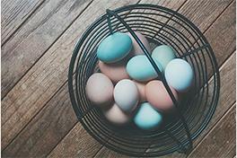 Bilde av en kurv med egg i forskjellige farber