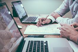 Nærbilde av skrivebord med to PCer og hender som skriver på et ark