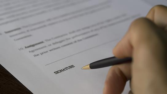 Nærbildet av en hånd som signerer på et papir