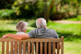 To eldre personer som sitter på en benk