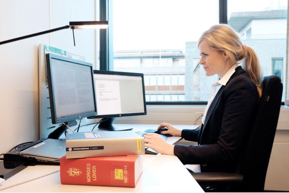 Nærbilde av en person som peker på PC-skjermen.