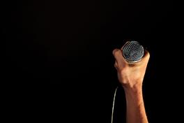 Nærbilde av hånd som holder en mikrofon